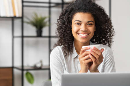 Smiling young cheerful African American woman with Afro hairstyle enjoying morning coffee while working on the laptop, sitting at the desk in the home office, happy businesswoman having coffee break Standard-Bild
