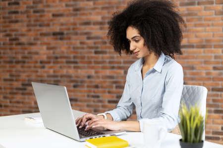 Portrait of focused mixed-race businesswoman with Afro hairstyle sitting at the desk against the brick wall and working on a project, typing on the laptop, concentrated on providing help to clients Standard-Bild