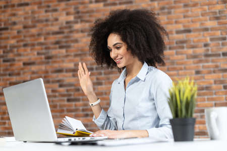 Smiling African American businesswoman in casual clothes with Afro hairstyle sitting at the desk, studying or working online, having a virtual meeting, saying hello, waving at the laptop screen Standard-Bild