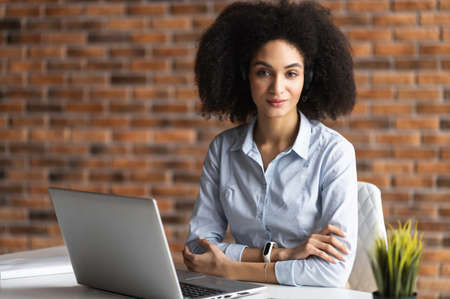 Young confident mixed-race woman with Afro hairstyle sitting at the desk in front of a laptop with arms crossed, looking at the camera, wearing business casual clothes, businesswoman at the workplace