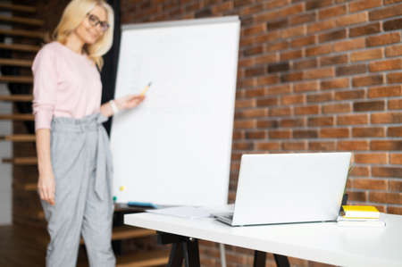 Mature female teacher, tutor coach in glasses with blond hair looking at the laptop screen, giving virtual lessons online by zoom conference call, or businesswoman presenting a project on a whiteboard