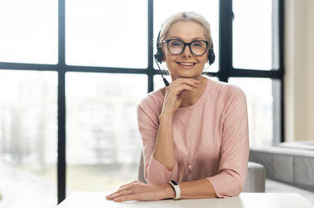 Portrait of a charming smiling elegant mature blonde woman or middle-aged customer service representative sitting at the desk against panoramic window, wearing headset, glasses, looking at the camera