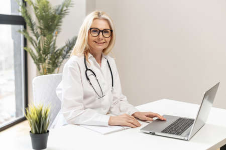 Mature female blonde doctor physician wearing glasses, white medical coat and stethoscope typing and filling up the medical form, watching online webinar seminar, sitting at the desk with the laptop