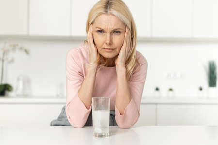 A tired mature blonde woman standing in the modern kitchen, touching temples, suffering from migraine or severe headache, taking medicine antibiotic or aspirin pill with a glass of water at home Standard-Bild
