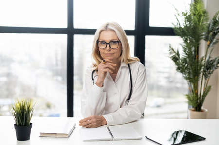 An intelligent mature female woman doctor with blonde hair in a white medical robe, glasses, and stethoscope sitting at the desk with papers, documents, notes, and green plants, looking at the camera