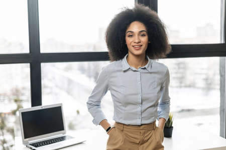 Successful confident young African American female entrepreneur businesswoman with Afro hairstyle in casual clothes standing with hands in pockets against window with panoramic view, looking at camera