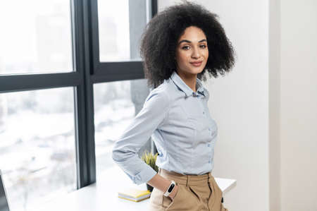 Portrait of a self made leader confident young mixed-race female entrepreneur businesswoman with Afro hairstyle in casual clothes standing with hands in pockets, leaning on the desk, looking at camera