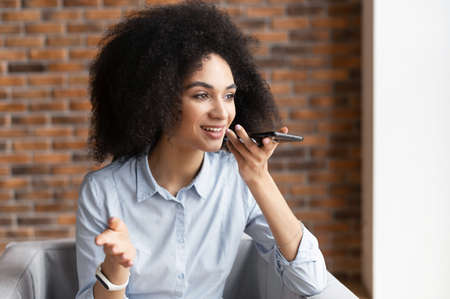 Young mixed-race ethnic businesswoman or female entrepreneur with afro hairstyle wearing casual clothes, sitting in the chair and holding a mobile phone, talking, gesturing, recording voice message