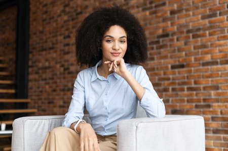 Successful confident young African American ethnic entrepreneur businesswoman with Afro hairstyle in casual clothes, sitting in the chair against brick wall, placed hand on chin, looking at camera