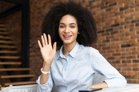 Friendly adorable African American female businesswoman freelancer with Afro hairstyle joyfully waving, smiling and saying hi, making hello sign, greeting participants of online conference, front view