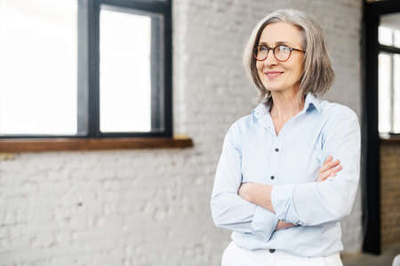 Confident and smiling old senior business woman wearing smart casual shirt and stylish eyeglasses stands with arms crossed in modern office space. A mature bossy lady, elderly purposeful leader Standard-Bild