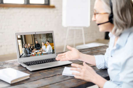 Group of people on the laptop screen, a mature coach wearing headset conducts an online webinar. Senior confident woman, manager explaining smth to online audience. Video conference, brainstorming