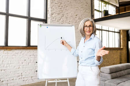 Senior woman wearing smart casual attire and stylish eyeglasses stands near flip chart and points to it. Webcam view an aged teacher conducts webinar, video meeting with an elderly business coach