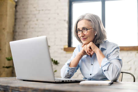 Intelligent elderly gray-haired businesswoman using a laptop in the office. Smart mature woman entrepreneur looks through emails, analyzes tasks, checks report. Senior online teacher conducts lecture