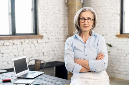 Serious and strict old senior business woman wearing smart casual shirt and stylish eyeglasses stands with arms crossed in modern office space. A mature bossy lady, elderly purposeful leader