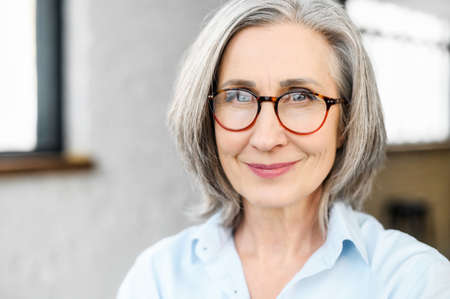 Close-up portrait of charming positive mature elderly business woman wearing stylish eyeglasses and smart casual attire. Senior confident grey-haired lady looks at the camera.