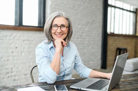 Intelligent elderly gray-haired businesswoman using a laptop in the office. Smart mature woman entrepreneur looks at the camera sitting at the desk. Senior online teacher, elderly female employee