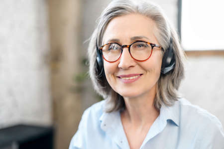 Headshot of confident and smiling old senior business woman wearing headset and stylish eyeglasses looks at the camera. A mature call center employee in touch, video chat with elderly support worker
