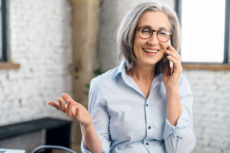 Smiling and positive senior businesswoman talking by the smartphone in the modern office. An elderly saleswoman has phone conversation. Mature female employee speaking on the mobile phone