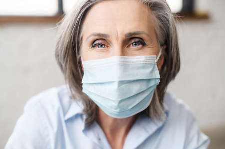Close up portrait of senior mature grey-haired business woman with a face covered indoor, elderly female office employee in mask staying safe on the workplace.