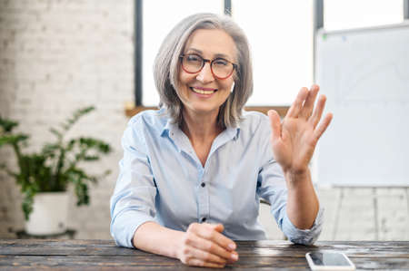 Video chat with a smiling senior elderly business woman. Webcam view of charming aged coworker, mature female colleague waving into camera, greeting participants. Video meeting concert Standard-Bild