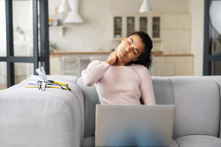 African American female freelancer or student with curly hair sitting on the couch in modern living room, feeling tired from constant work on laptop, removed her glasses, stretching neck with hand