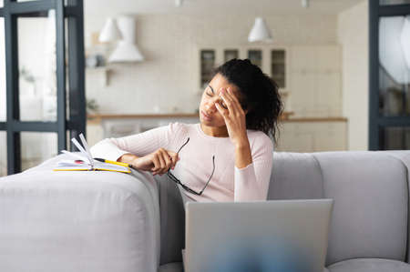 Mixed-race female freelancer or student with curly hair sitting on the couch in modern living room, feeling tired from constant work on laptop, removed her glasses, touching head, having a headache