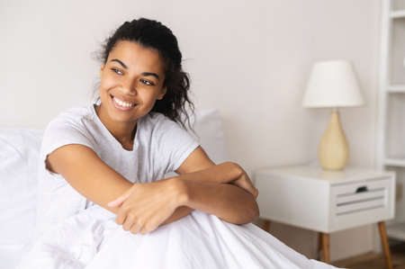 Positive young relaxed mixed-race woman covered with cozy warm soft blanket sitting down in her pajama and staying at home, daydreaming, resting and looking away, enjoying day off or a weekend in bed Standard-Bild