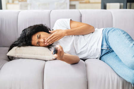 Young mixed-race girl in casual clothes relaxing resting lying down on the couch at home, feeling bored and sleepy, yawning, pointing with a tv remote controller at the camera, and switching channels