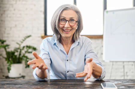Happy friendly senior female teacher manager with pleasant smile in earphones and glasses looking at camera, sitting at the desk, gesturing and talking online, the view while video calling concept