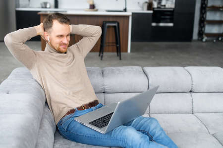 European successful man with earphones sitting on the comfortable pure sofa, smiling, relaxing after productive day with a laptop on the lap, holding hands behind head, happy to end all planned Stock Photo
