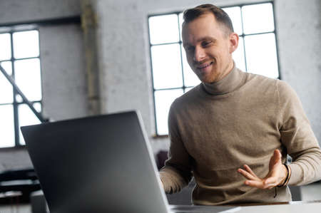 Neat mature businessman with light brown hair and short beard sitting at the laptop and talking by video with new customers or investors, in new unfinished office, full of enthusiasm and inspiration