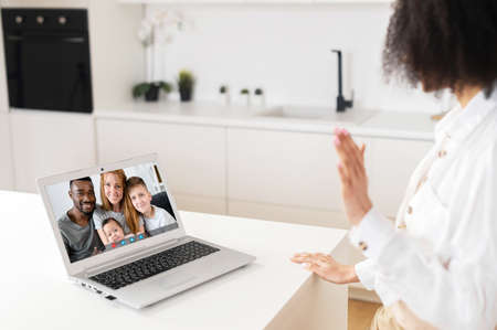Focus on screen with happy multiracial family, making video call with grown up young daughter woman or sister, chatting communicating online using computer application, staying at home on isolation Stockfoto
