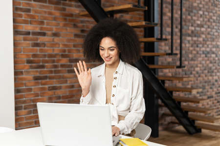 African American attractive woman at laptop chatting via video at home, happily greeted with a friend, long-distance relationship, self-isolation during the quarantine, new reality, virtual meeting
