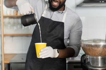 Close-up biracial barista preparing latte coffee to go, a multiracial waiter pouring milk into paper cup, take-away hot drinks order, cropped picture