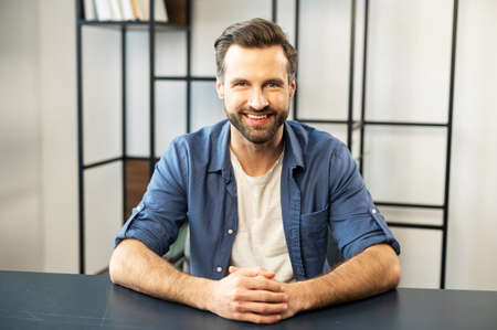 Portrait of smiling businessman with bristle and charming smile, sitting at the desk at modern office, dressed in white t-shirt, denim shirt, freelancer, owner of a new startup, successful leader 版權商用圖片