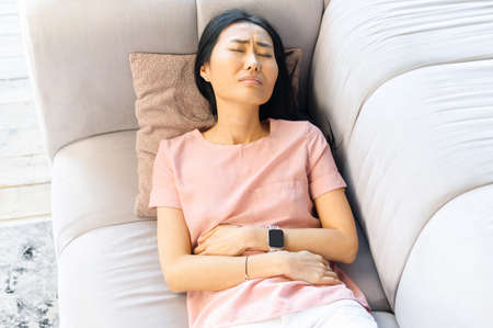 Young Asian mixed race woman wearing casual clothes suffering from menstrual pain, feeling sick to her stomach, holding belly, experiencing abdominal cramps during period, lying down on bed at home Stockfoto