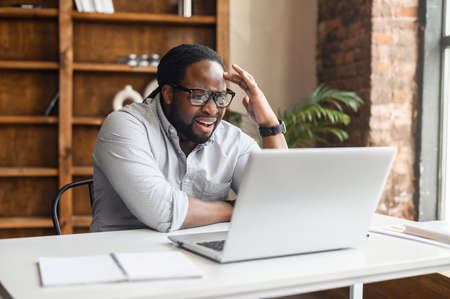 Frustrated mature african unshaved entrepreneur in black glasses with sad grimace in front of laptop in office, noticed a big mistake he did, touches his head with his hand, wearing casual clothes
