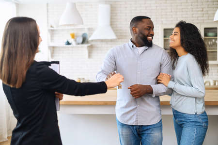 A real estate agent is giving the keys to a happy African-American couple, a biracial newlyweds bought new apartment, got a mortgage, a couple relocated, moving in own house