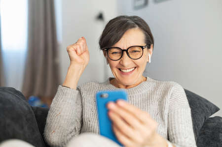 Glad senior mature elder lady wearing eyeglasses sitting on the couch in the living room, looking at the mobile phone, excited to read good news, lucky lottery winner, passed the exam, victory concept