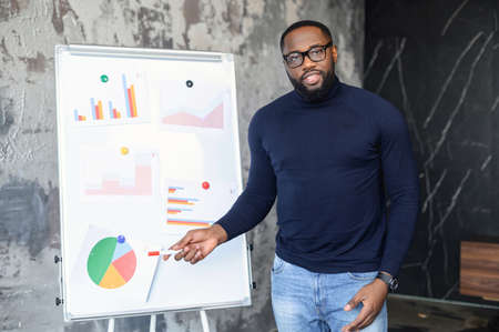 Male worker showing a presentation to his bosses, standing near white board showing diagrams, on business training, meeting or seminar, indicates and explains diagram, gives report about statistics