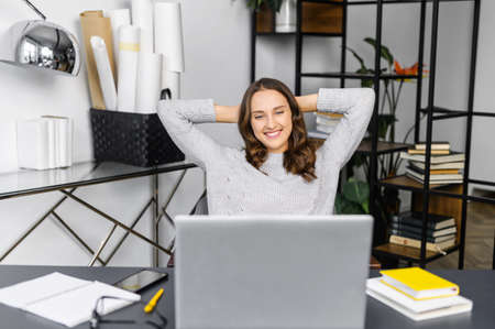 Satisfied young woman leaned back in front of the laptop sitting at the office desk, female employee in casual wear rejoyce finished project, looks at the screen, smiles, takes a break on a workplace