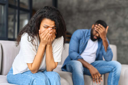 Young biracial couple relation problem concept, african woman feeling sad and crying after have an argument at home, sad or depressed woman sitting on sofa with her couple, man in defocus sits near
