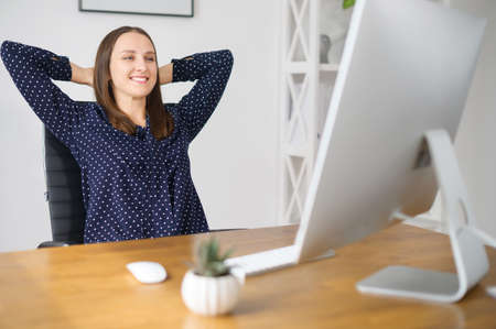 Smiling female employee takes a break on the workplace in the office, leaned back in the chair rests with satisfied face expression, woman rejoices with finished project or workday over