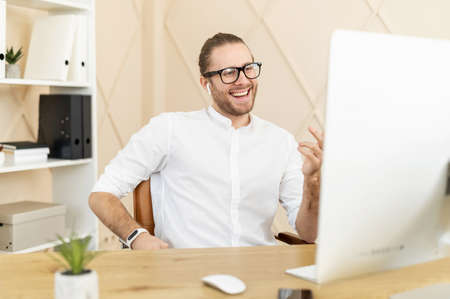 Smiling male office employee has pleasant video meeting, virtual conference with a team, confident hipster wearing white shirt and glasses looks to PC webcam and talking at ease