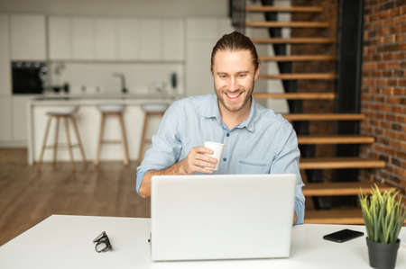Cheerful millennial guy works on outsours, using a laptop for receiving emails, conducts correspondence with customer, develops software working remotely from home, drinks coffee and smiles