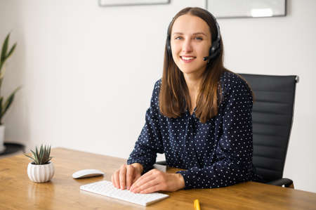 Portrait of smiling and positive young female call center operator, cheerful woman wearing headset sits in the workplace and looks in the camera