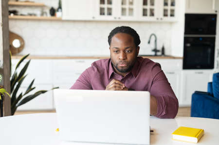 Concentrated African-American guy with dreadlocks staring at computer monitor sitting at the desk in home office, focused black man solving business tasks working with laptop remotely from home