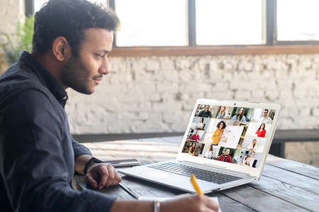 E-learning corporate training. Mixed-race indian man using laptop computer for watching online courses, webinars, takes notes, group of diverse people and female tutor with a whiteboard on the screen