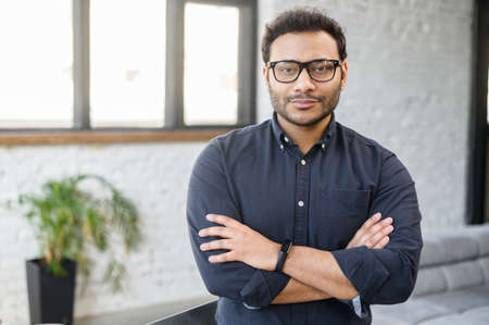 Ambitious hindu man in smart casual shirt stands with arms crossed in contemporary office space and looks at camera, portrait of purposeful indian businessman, ceo indoor. Diversity of office staff